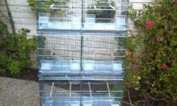 FOUR Breeder Cages new in the box each cage has 2 large doors on cage front ,4 feeder doors per unit ,4 feed dishes per cage Outside access to feed dishes Comes with wire divider ,4 Wood per unit Nest box door on both ends of each cage Metal bottom pans